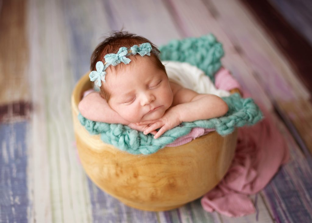 newborn baby girl sleeping in bowl