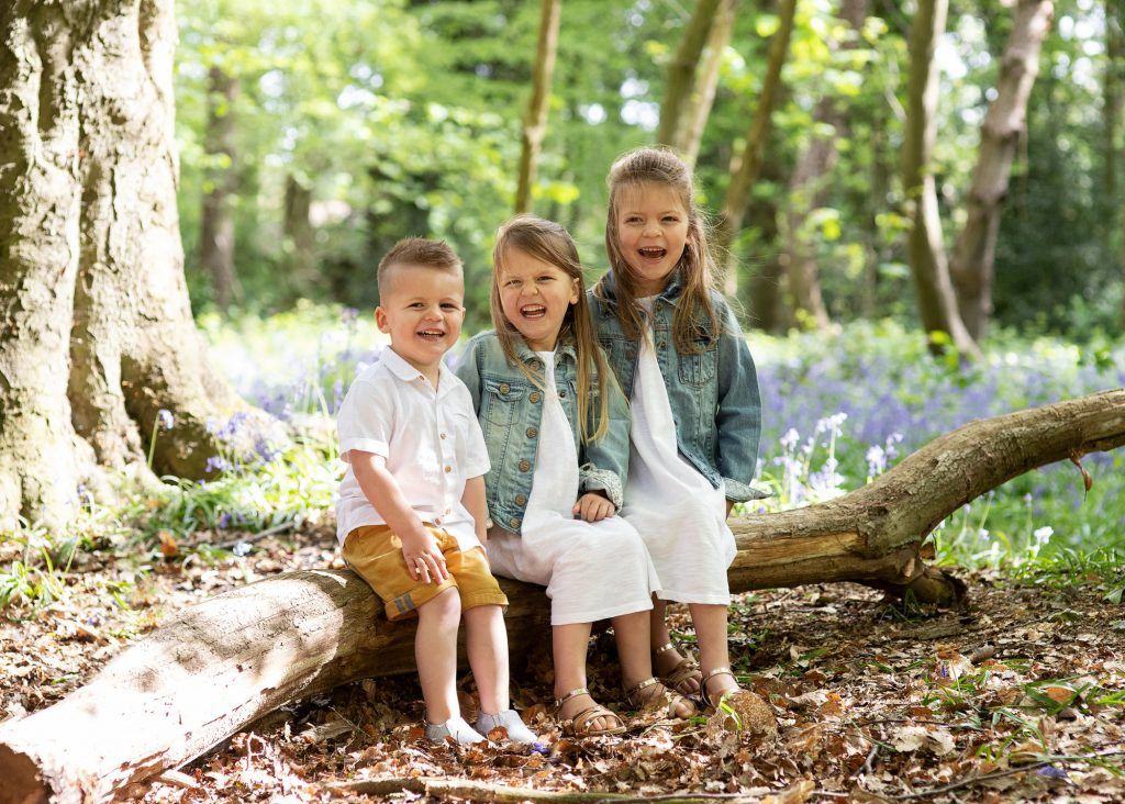 outdoor family photoshoot boy and two girls in bluebells