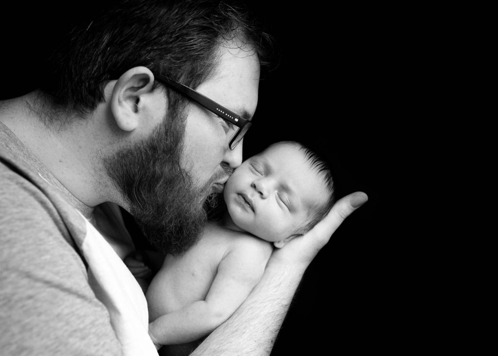 dad with big beard kissing newborn photographed in kent