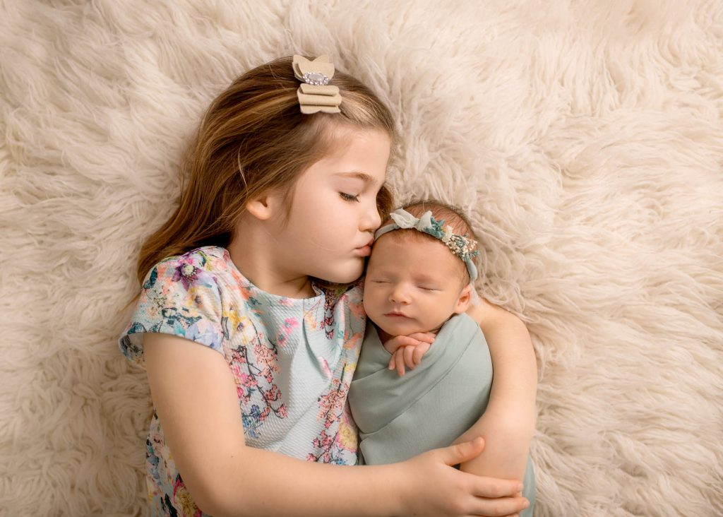 girls holding newborn sister