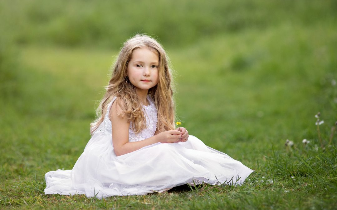 girl sitting in field with yellow flower
