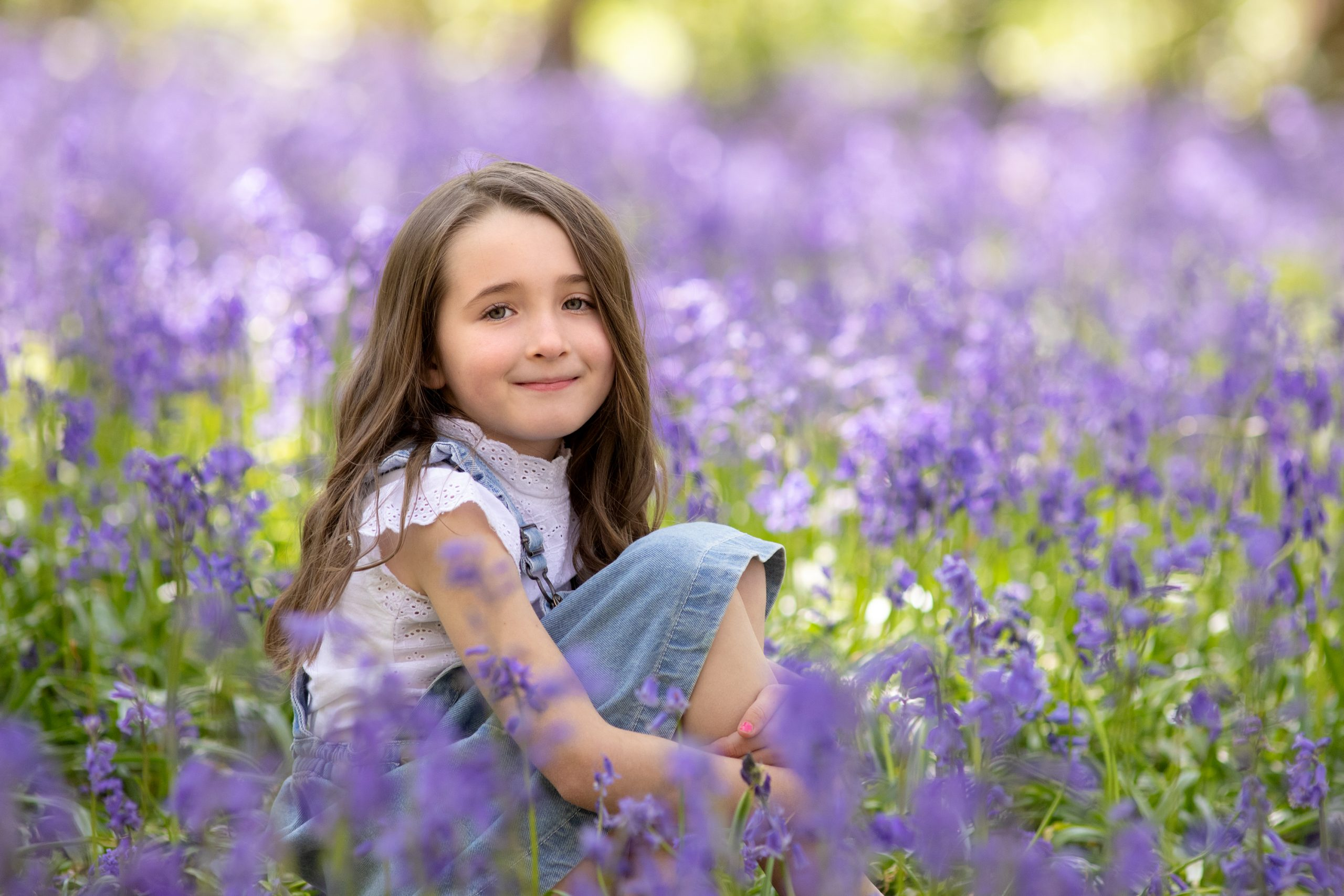 outdoor family photoshoot girl sitting in bluebell wood