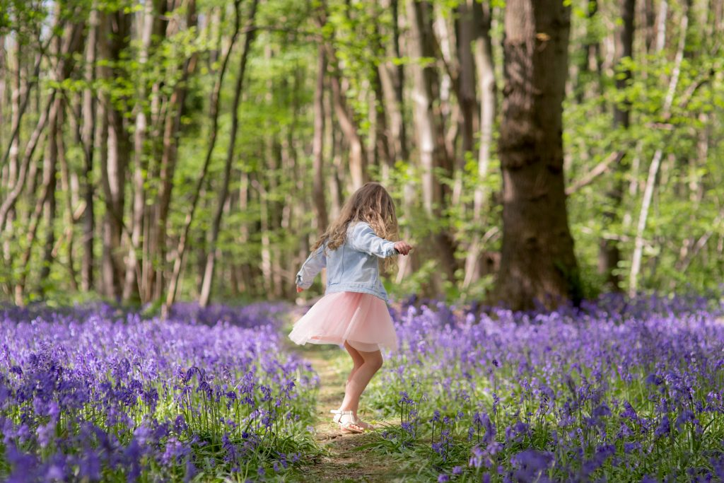 girl dancing in bluebell wood
