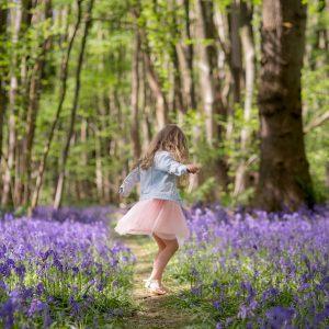 girl dancing in bluebell wood