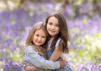 Sisters among the bluebells during a family photoshoot in Kent