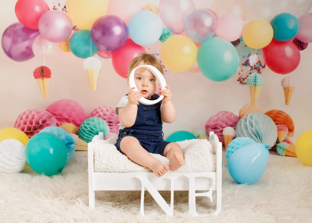 boys first birthday holding a wooden letter, sat on a wooden bed with balloons