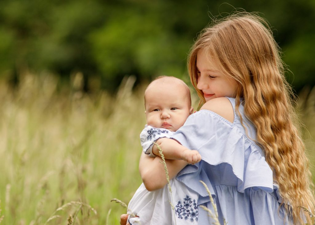 sister cuddling baby in the park in Kent