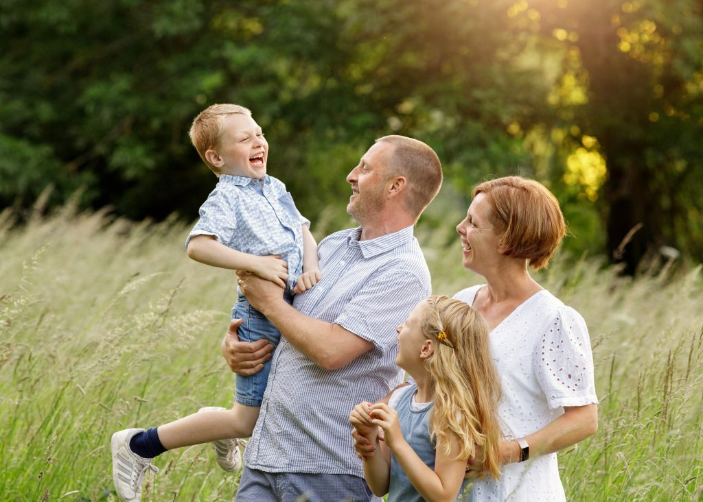 family lifting boy up laughing outside in the park