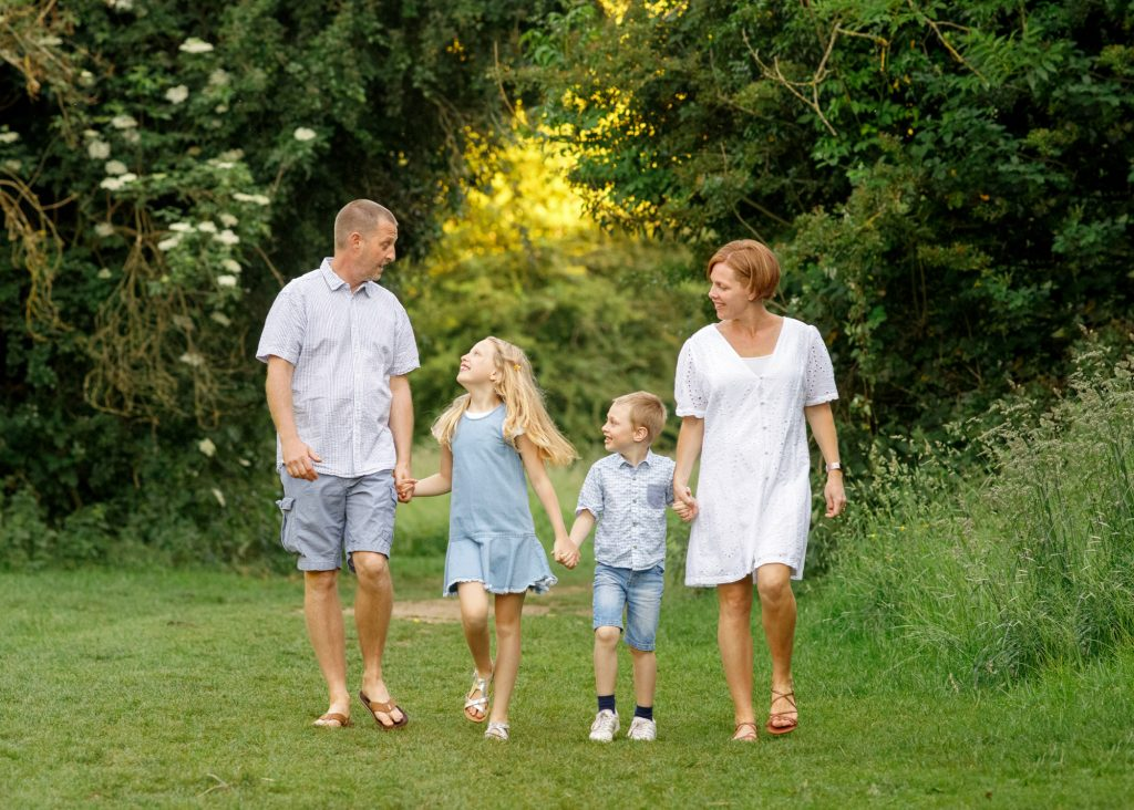 family walking in the park wearing white and denim clothes photographed in kent