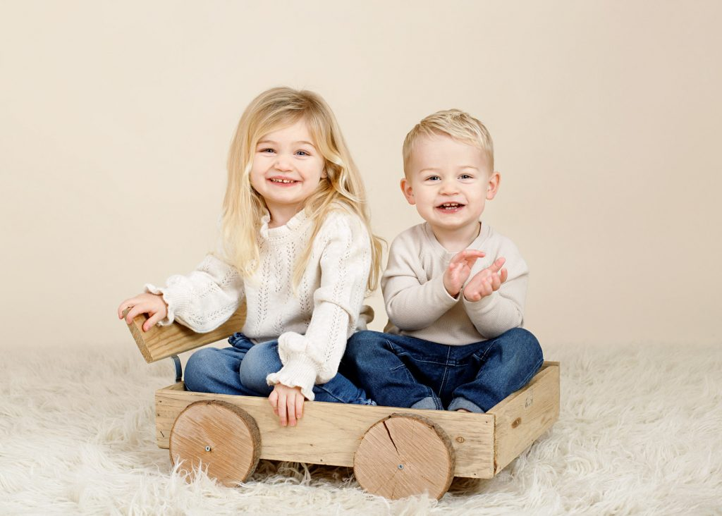 boy and girl sitting in a wooden wagon