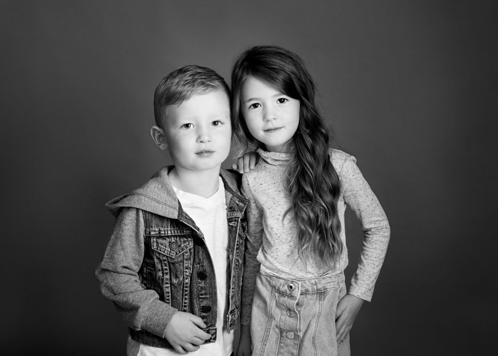 black and white image of boy and girl looking at camera
