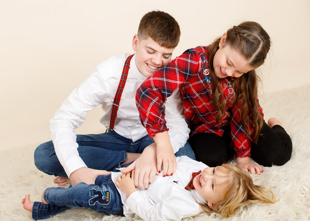 girl and boy tickling little brother on a cream rug