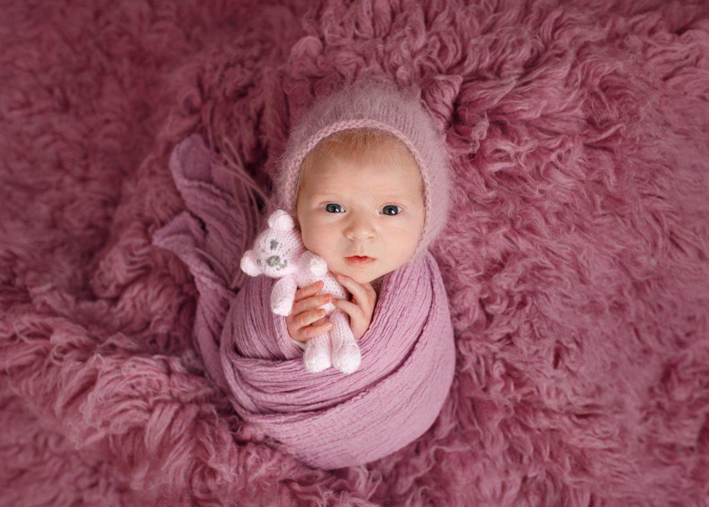 baby with purple bonnet cuddling pink teddy