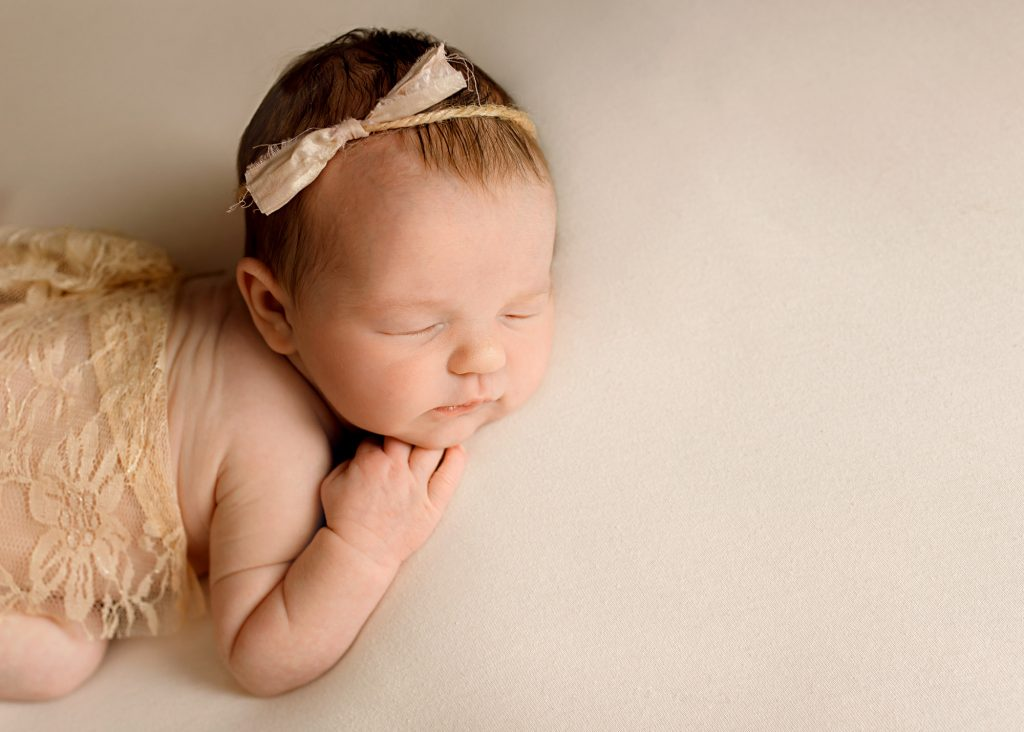 baby girl with beige bow in her hair photographed in Kent