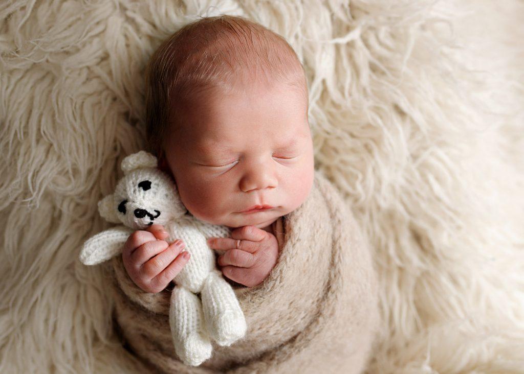 baby hugging teddy