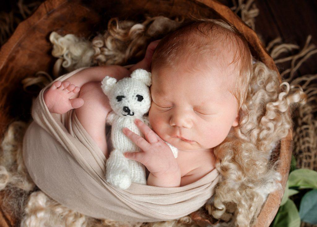 baby boy cuddling cream teddy