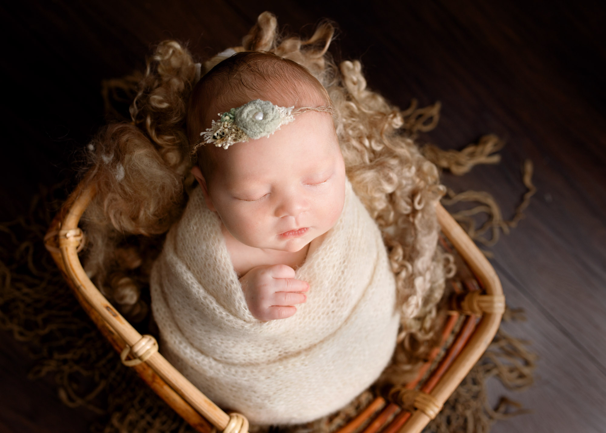 baby girl wrapped in cream blanket in a bamboo basket