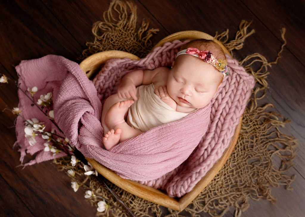 baby laying in heart bowl wrapped in purple blankets