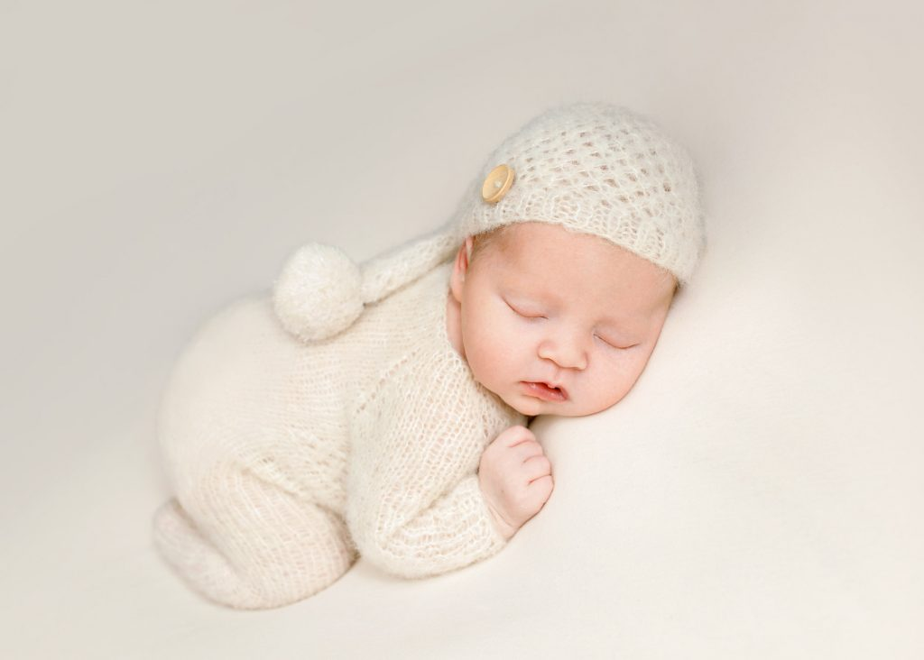 baby with cream knitted hat and romper