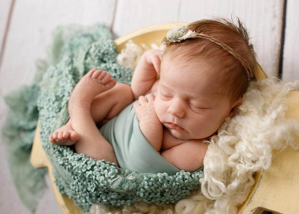 newborn girl curled in a bowl on green lace photographed in Kent