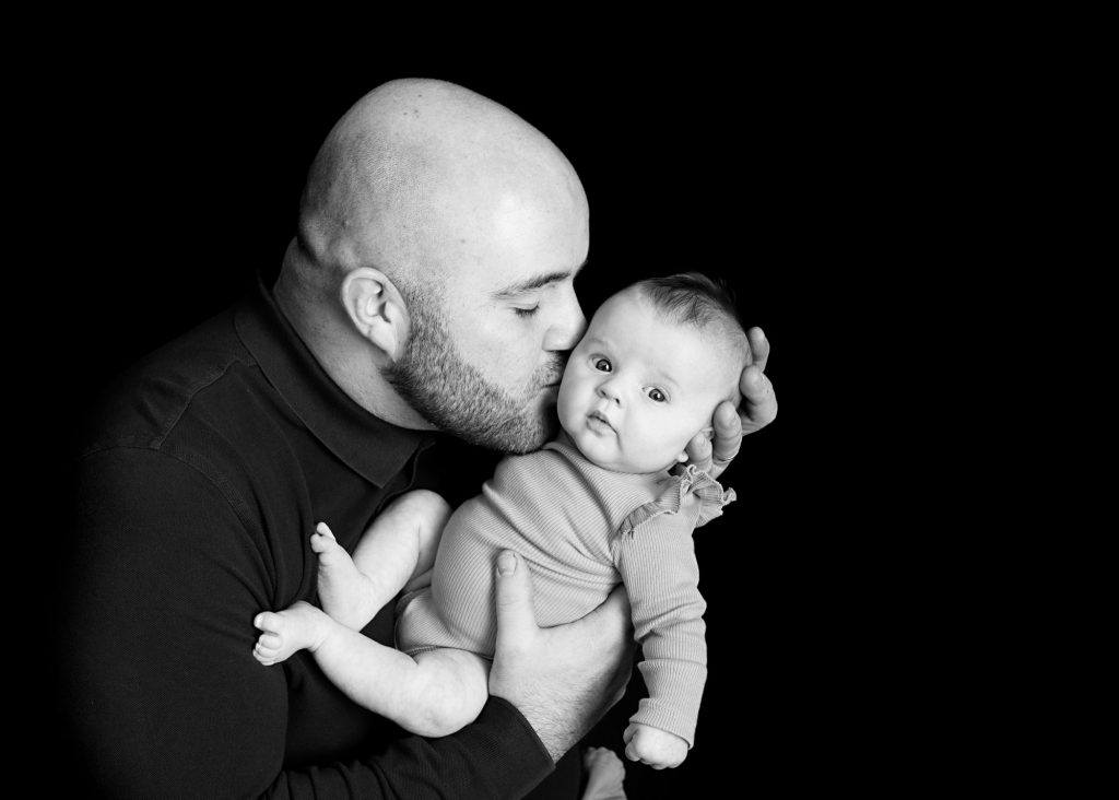 daddy kissing baby on the cheek