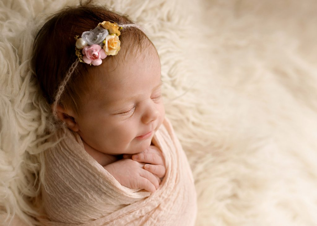 newborn baby girl wrapped up in pink photographed in Kent