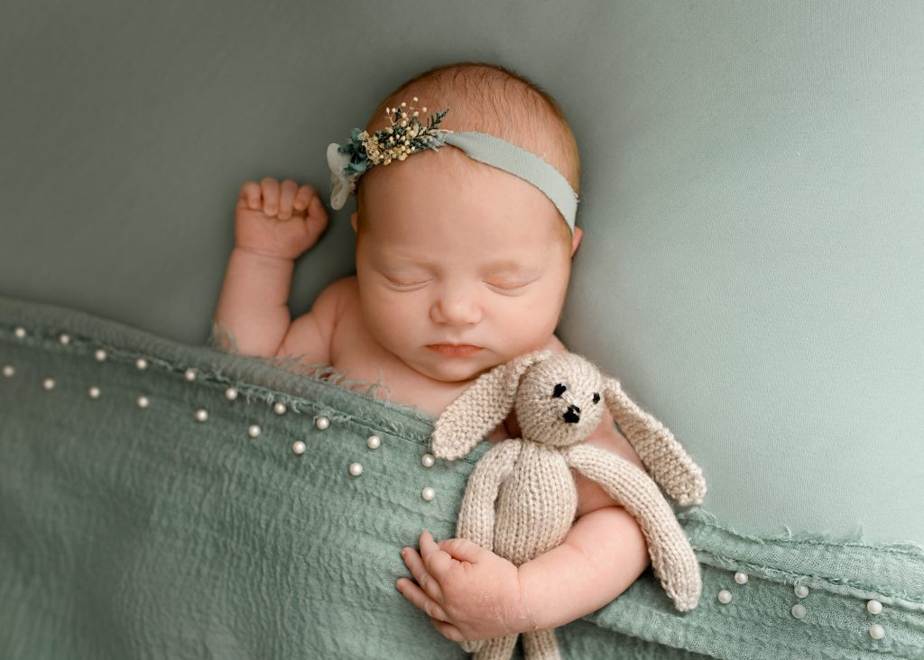 baby cuddling her teddy wearing a green headband photographed in Kent