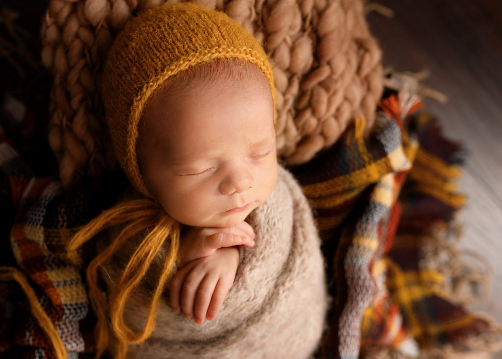baby with mustard bonnet on a check blanket photographed in Kent