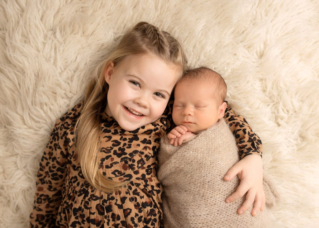 sister and baby brother laying on a cream rug