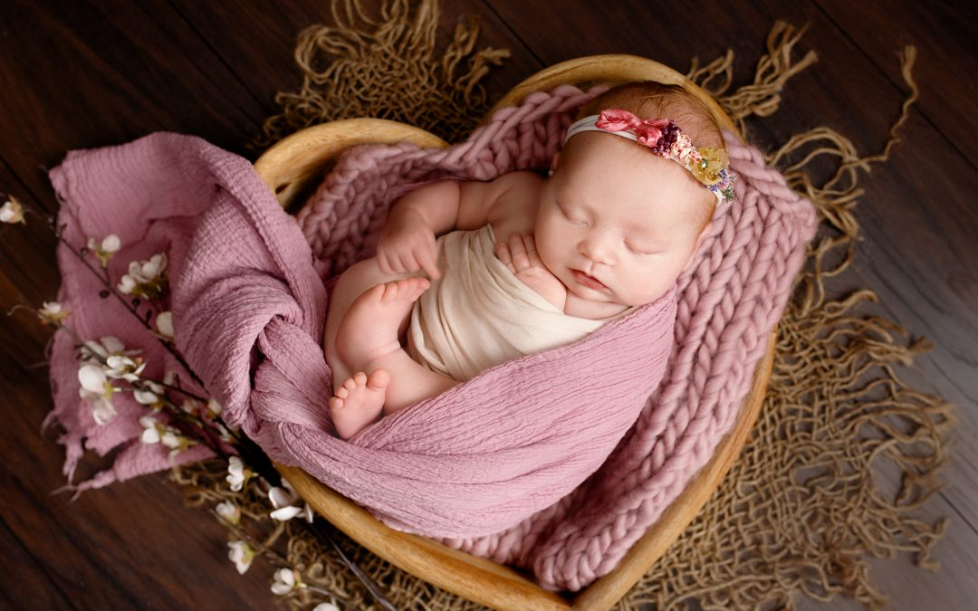 newborn baby girl laying in wooden heart born wrapped in purple