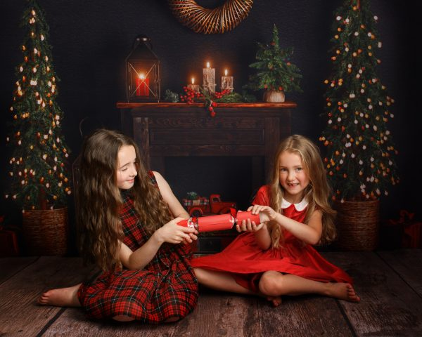 two girls pulling Christmas cracker during a photoshoot in Kent
